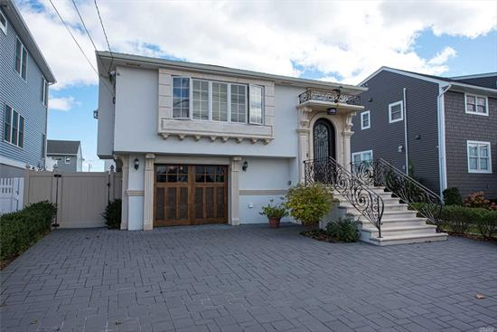 This spectacular home is perfectly positioned on canal to enjoy scenic views of the Great South Bay. Exquisite European architectural details set this home apart. Features include 40 ft bulkhd, highest quality stucco & masonry construction, imported marble gas fp, marble entry, wrought iron railings, crown moldings, mahogany cabinetry, high efficiency high end windows, doors and appliances. Low taxes, Low flood ins, Elevation certificate. Close to town, train & beach. Don't miss this one!