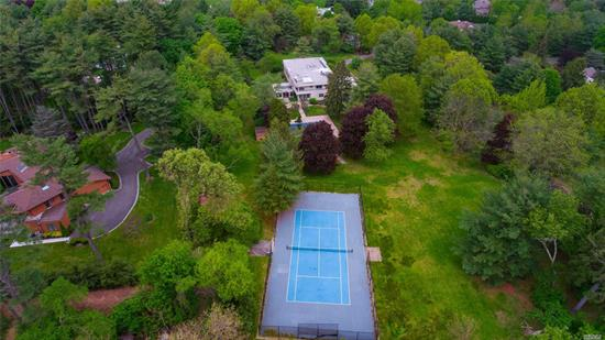 Old Westbury. Charming Contemporary Sitting on Over 4 Acres in The Heart of Old Westbury. This 7-Bedroom, 6.5-Bath Home Features An Open Floor Plan, With Generous Sized Rooms, Tons of Natural Light Shining Through Walls of Glass, Dramatic Entry Foyer With High Ceilings & 2nd Floor Balconies, And Incredible Flow. With Travertine Marble Staircases & Columns, First Floor Master Suite With His & Hers Custom Walk In Closets, Inground Saltwater Pool, And Tennis Court, This Home is Sure To Please!