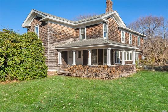 Circa 1900 Cedar Clad North Fork farmhouse on coveted Peconic Lane, home to statuesque B&B & antique estates. All Hardwood w/gracious common rooms-library, parlor, formal LR, formal DR, music room & heated sunlite morning coffee side porch, expansive kitchen/pantry & powder room, upstairs 5 BR's plus nursery/maids room/or additional bath. Many period details & trimwork. 1/2+ acre with detached garage and 2 storage buildings. Natural Gas heat. An antique home to pull at your heart strings!