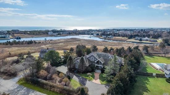 QUOGUE SOUTH ESTATE SECTION - Best waterfront value in the heart of Quogue village set on two private manicured acres, canal front with deep water dock, golf course view, gracious open living space, four en-suite bedrooms, 20x50 pool, Exceptional Value!