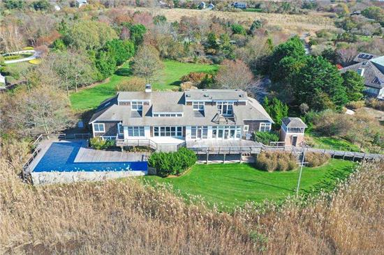 Nestled in a private corner of East Moriches, this almost 6-acre property on the open bay is one to see. Complete with full tennis court, waterfront pool, private beach, & dock, this property is perfect for the whole family. Cook delicious meals in the open floorpan chef's kitchen featuring water views. Curl up with a book on the expansive porch or 1 of the 2private master suite's verandas. Flooding natural light makes every day feel like a vacation in this spacious 5 BD, 5.5 BA home.