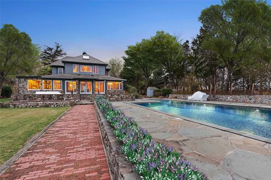 Set on 2.5 private acres, sits a beautifully kept 4-bedroom 4-bath farmhouse showcasing breathtaking views of Tuthil Cove. An open and inviting living space features a wall of glass doors offering picturesque views. leading to a chef's kitchen with stainless steel appliances. Outdoors, there is a detached game room garage, tennis court, pool, and a brick pathway leading to a boat dock able to accommodate a 50ft boat. A stone pathway leads to a separate charming 1-bedroom, 2-bath cottage.