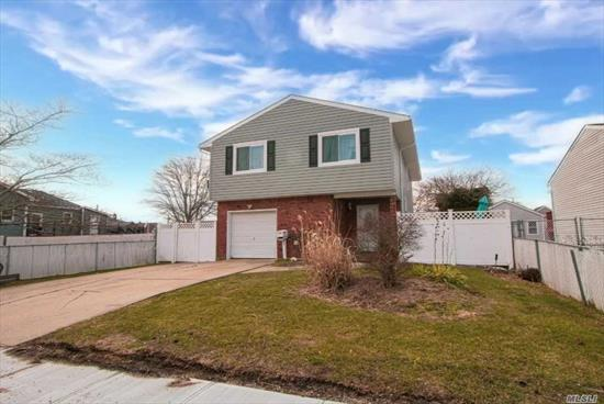 Lovely In-Line Hi-Ranch, ground-level entrance leads to a large entry hall, with laundry room & garage access. The second floor offers an open flow with spacious EIK, Dining Room & Living Room, Master with Full Bath & 2 more Bedrooms & Full Bath. The first floor features a large open family room with a kitchen, bedroom, and full bath. Other features include hardwood floors, updated windows & siding, in-ground sprinklers, rear covered deck perfect for outdoor entertaining and much more.