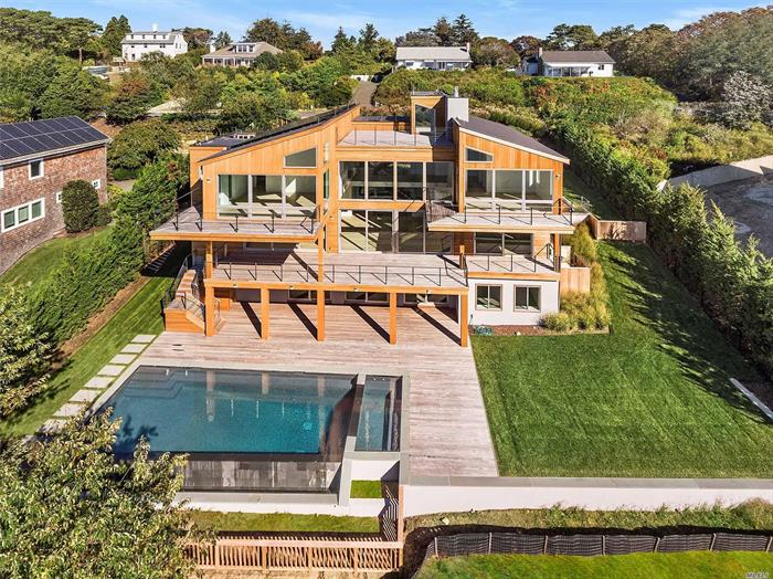 Dream location marries master craftsmanship at Southampton waterfront property creating perfection. Now just waiting someone special to call it home. This hip beachfront getaway provides an elevated waterfront lifestyle. With a bit of West Coast vibe and with more than 6, 000 square feet, this 3+ level Modern creation is nestled perfectly into the bluff. Enjoy incredible views of Shinnecock Bay and the Atlantic Ocean from every room. Everyday is a new canvas. Come see today