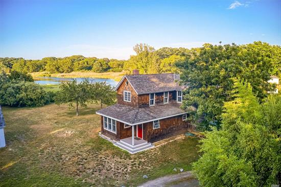 Mattituck, North Fork: Opportunity knocks: authentic and sophisticated farmhouse on approximately 2 acres (two separate deeds w/each lot one acre and approx 170' & 120' on creek individually) with approximately 290 feet of water frontage on Mattituck Inlet/on Long Creek Branch. Bright sunny location close to Love Lane and other village amenities. Gorgeous AGA kitchen; Living room with French doors and Fireplace/wood burning stove. 3 bedrooms 1.5 baths.  Large 2 car garage PLUS large outbuilding barn. Close to area beaches and vineyards. Create your North Fork legacy at this spectacular waterfront compound property.