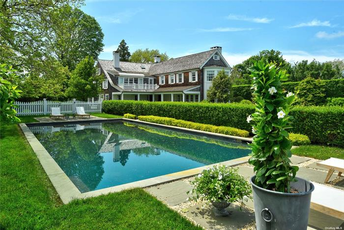 Graceful and refined living in Georgica, South of the Highway in East Hampton, takes place on one-and-a-half acres. As you enter the foyer, a bright blue living room with fireplace greets you as well as the formal dining. There is an intimate study for quiet reading in front of a cozy fireplace. Toward the back of the house is the stunning kitchen with an open living space with fireplace fronted by a wall of French doors and windows to view the lush expansive green lawn. The estate has seven bedrooms: the second floor has a dreamy master suite with fireplace along with three more pretty guest bedrooms with ensuite baths. The third floor has two cheerful bedrooms with bath. A private guest cottage with pergola has a kitchenette and lovely bedroom with ensuite bath.  On summer nights choose from the wisteria pavilion or the covered portico for alfresco dinning. A Gunite pool and playset complete a wonderful destination.